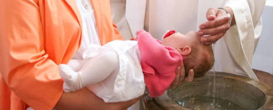 Pfarrer Thomas Winter tauft ein Kind. Er schöpft das Wasser mit der Hand aus dem Taufbecken und lässt es über den Kopf des Kindes laufen.